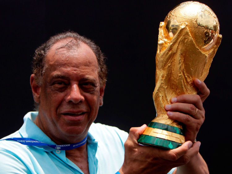 Former Brazilian soccer captain Carlos Alberto Torres holds the 2014 FIFA World Cup Brazil trophy during its unveiling ceremony at a Soccerex event in Rio de Janeiro